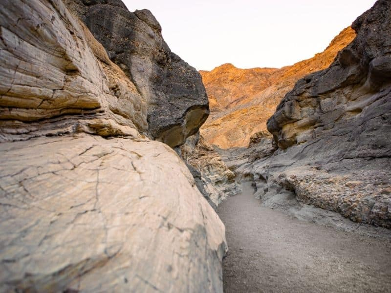 the slot canyons of mosaic canyon with sandy ground and orange and whiteish brown rock