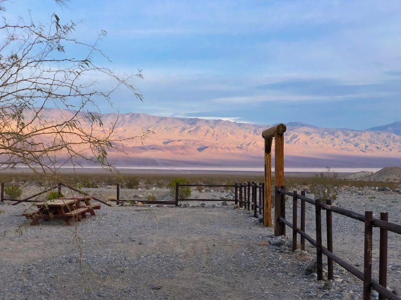 panamint springs campground with an empty picnic table and light on the mountains