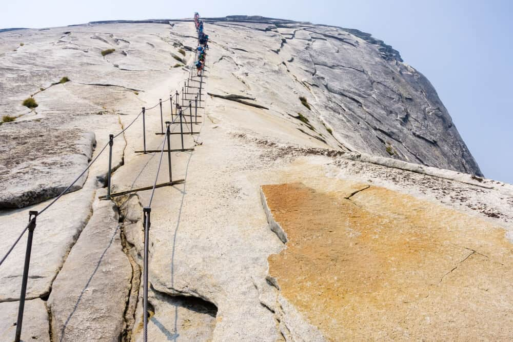 people climbing up the cables of half dome in yosemite, close up of the cables people use to climb to the top