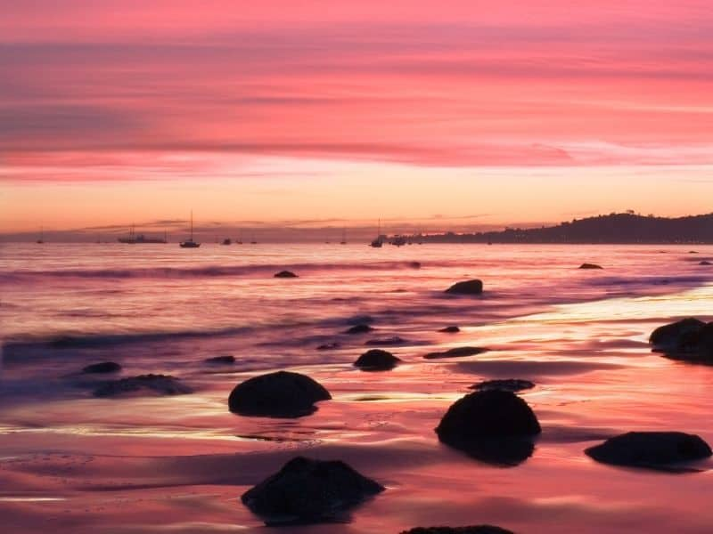 butterfly beach in santa barbara with brilliant pink and orange sunset colors and rocks on the beach shore and sailboats in the distant waters