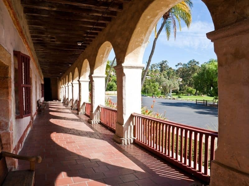 the archways and railings of the santa barbara mission with palm trees in front
