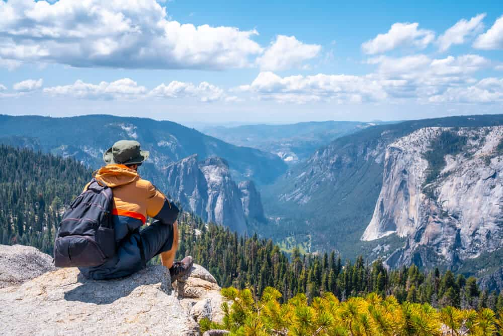 man with green hat, orange jacket and backpack sitting at sentinel dome viewpoint looking onto valley, trees, and other granite domes in yosemite