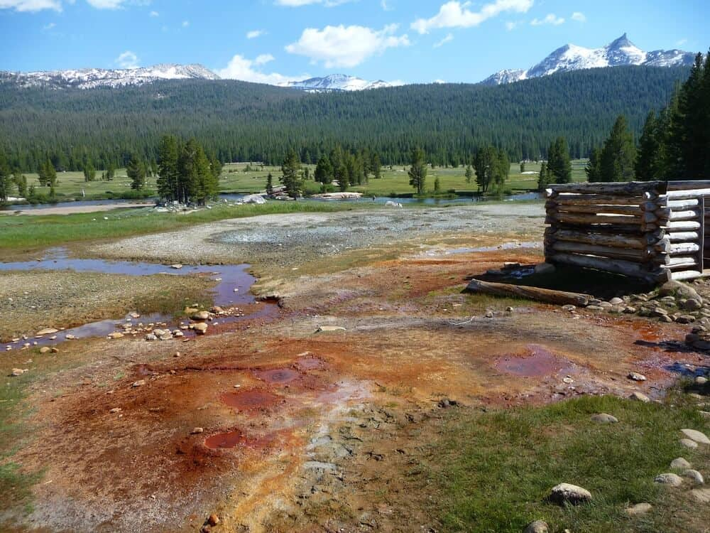 springs in yosemite, reddish-looking deposits around spring water, mountains in the distance