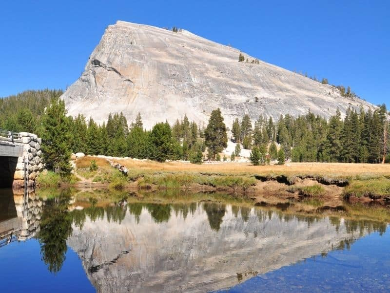 a large granite dome looming over a lake with a perfect mirrored reflection