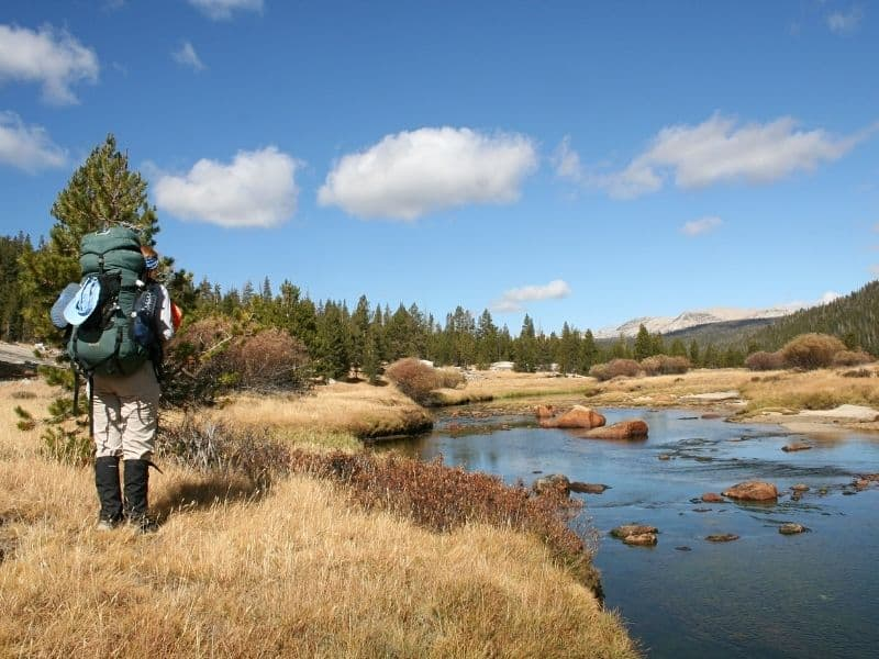 a hiker with a backpack standing by a creek in tuolumne meadows hiking alongside the john muir trail