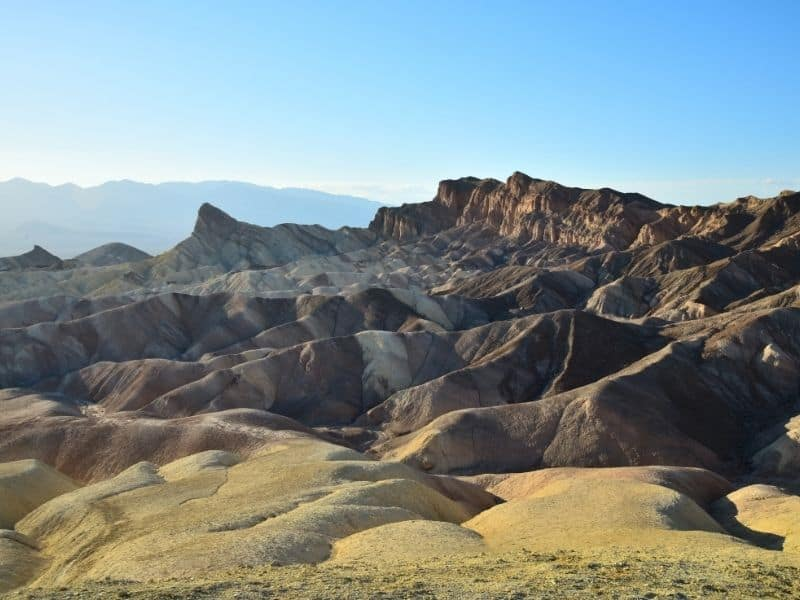 the colorful yellow brown and white rocks of zabriskie point in the later afternoon sun