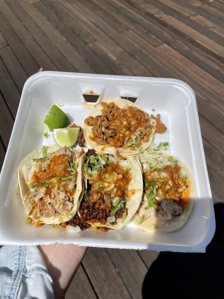 a styrofoam tray with four tacos