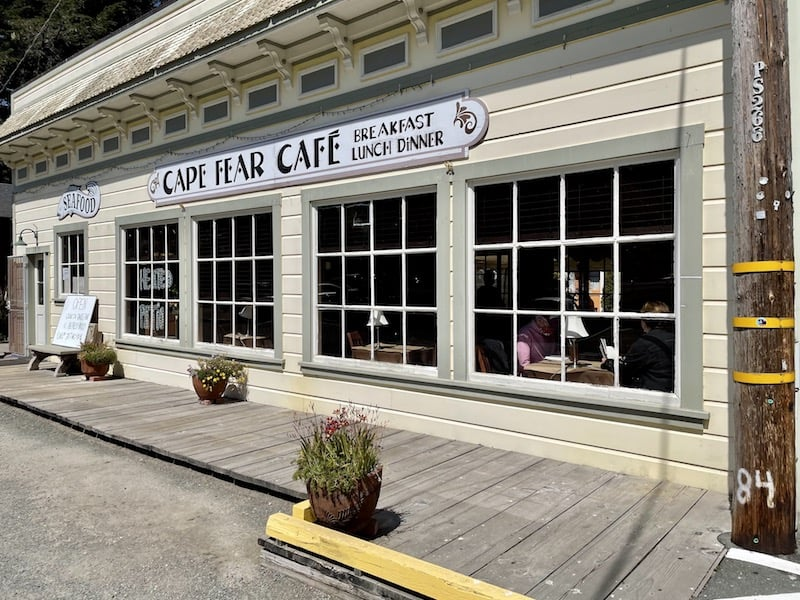 a pale-yellow painted restaurant with the sign that says 'cape fear cafe breakfast lunch dinner'