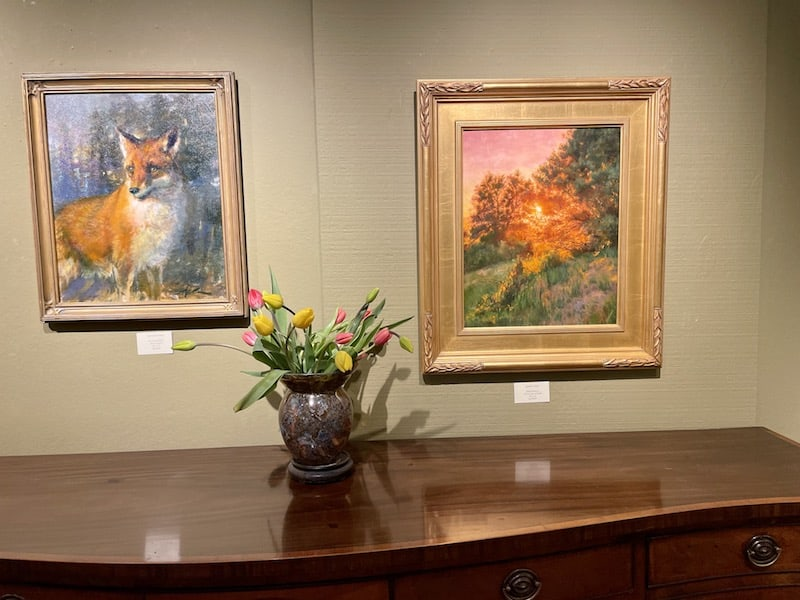 two landscape paintings and a vase of tulips.
