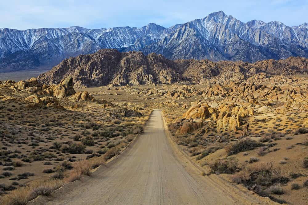 view of the famous road to the Alabama hills with a dirt road leading to the mountains and hills
