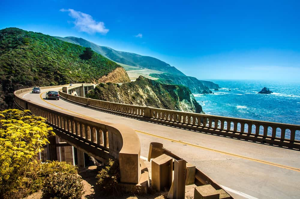 road tripping through big sur, crossing bixby creek bridge en route to the most scenic big sur hikes