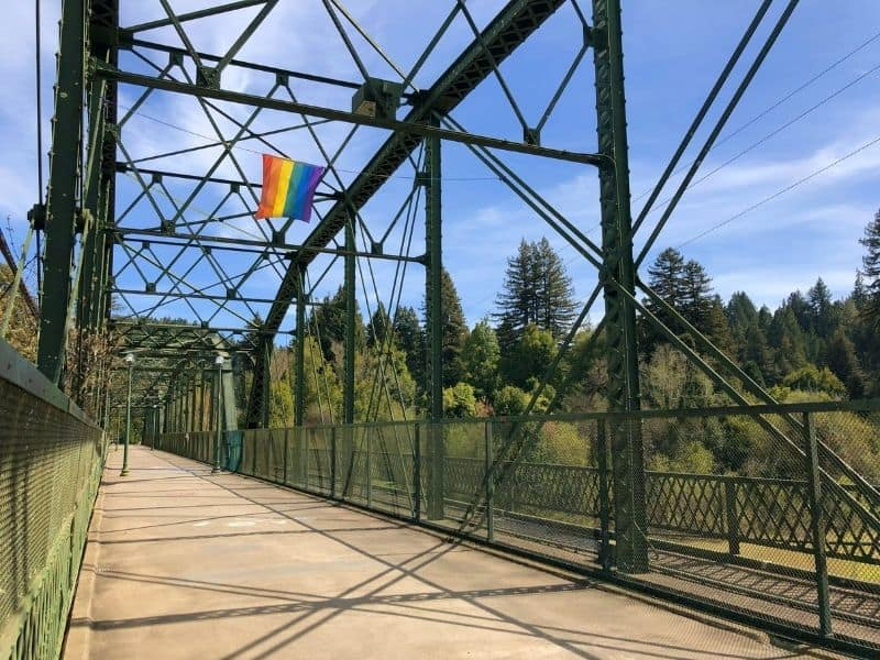 bridge with a rainbow flag on it over guerneville