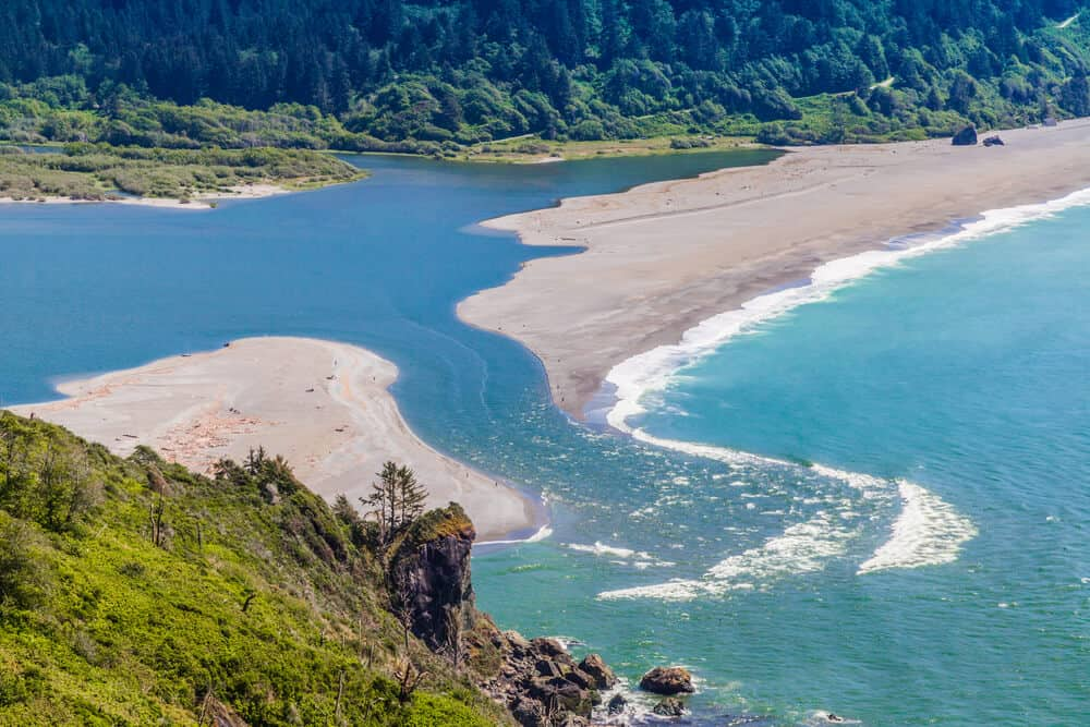 Klamath River emptying out into the Pacific Ocean, breaking apart a beach into two parts