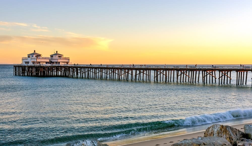 photo of the malibu pier at sunset with the pacific ocean illuminated by sunset colors