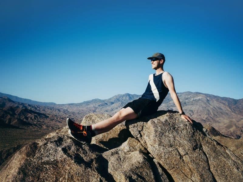 man sitting atop rocks at the summit of Murray peak aka murray hill