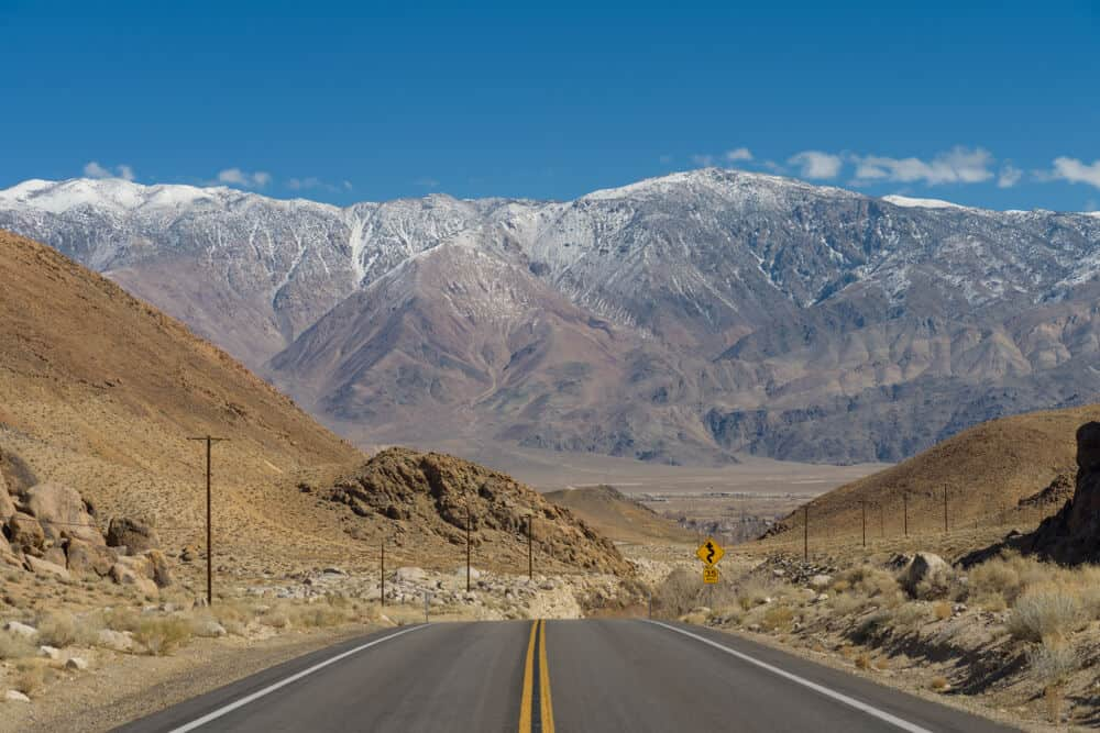whitney portal road heading towards the alabama hills with enormous sierra nevada mountains looming over the road