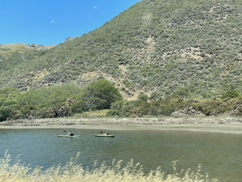 Two kayakers out on the water in Tomales Bay