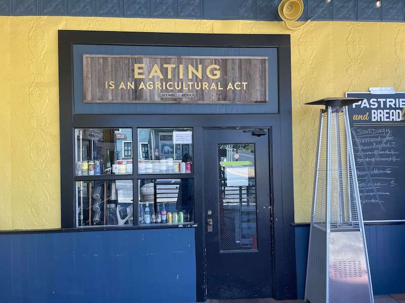 sign that reads 'eating is an agricultural act' on a yellow wall