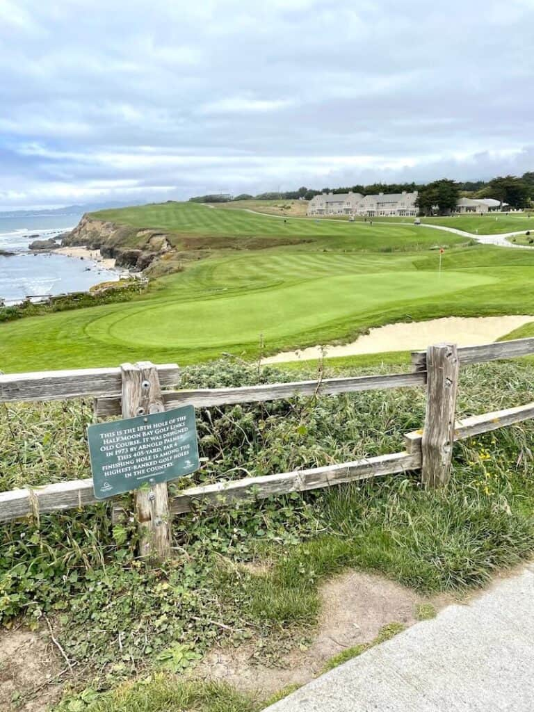 View of the historic 18th hole of the Old Course of the Half Moon Bay Golf Links with an information sign and the Pacific Ocean in the background.