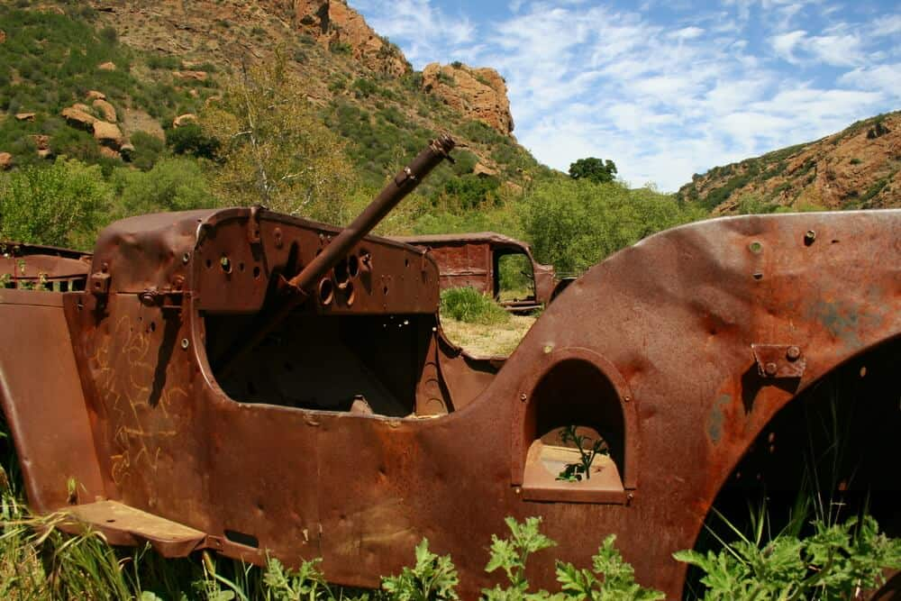 Rusted vehicle at the endpoint of a popular hike in Malibu on a partly cloudy day