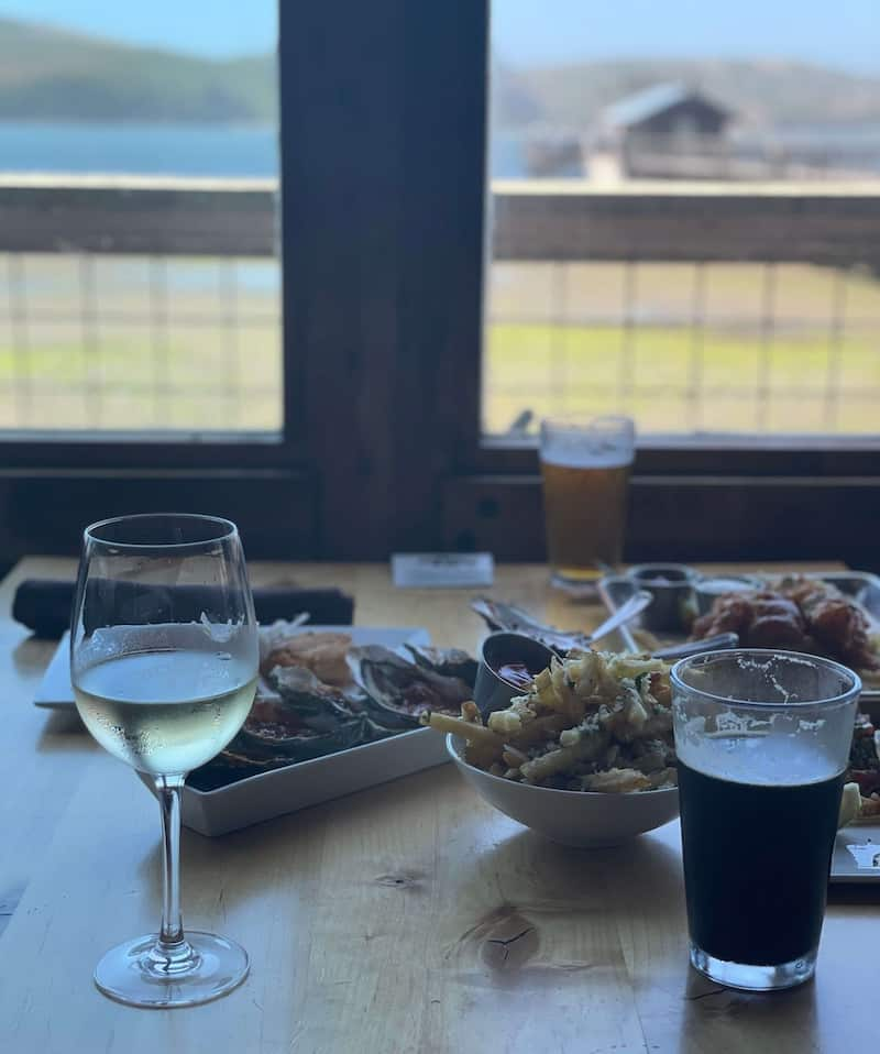 A meal eaten inside at Nick's with wine, beer, fries, and seafood