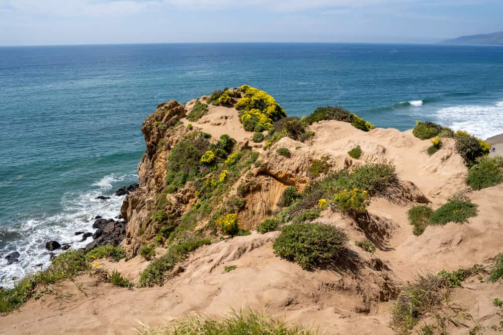 Point Dume endpoint of Malibu hike looking over the blue waters of the Pacific Ocean on a sunny day in Malibu