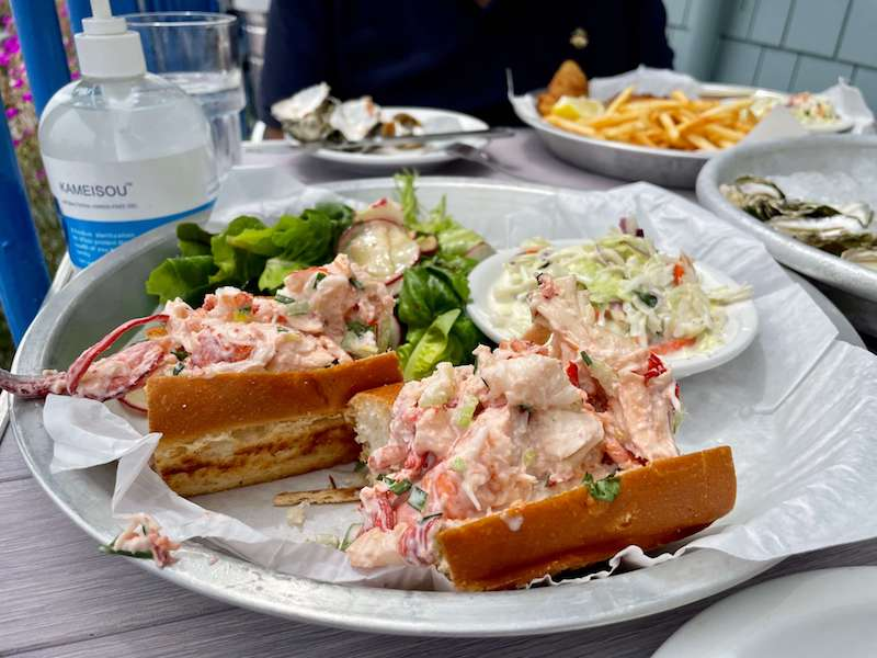 a delicious lobster roll with salad and fish and chips in the background