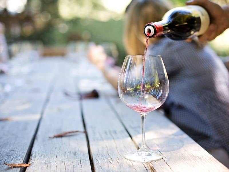 a hand pouring a glass of red wine at a napa wine tasting while sitting at a large outdoor table