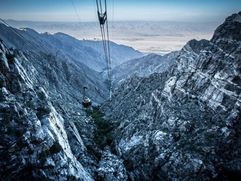 aerial tramway in palm springs with snow covering sides of the canyon as you go up to mt san jacinto