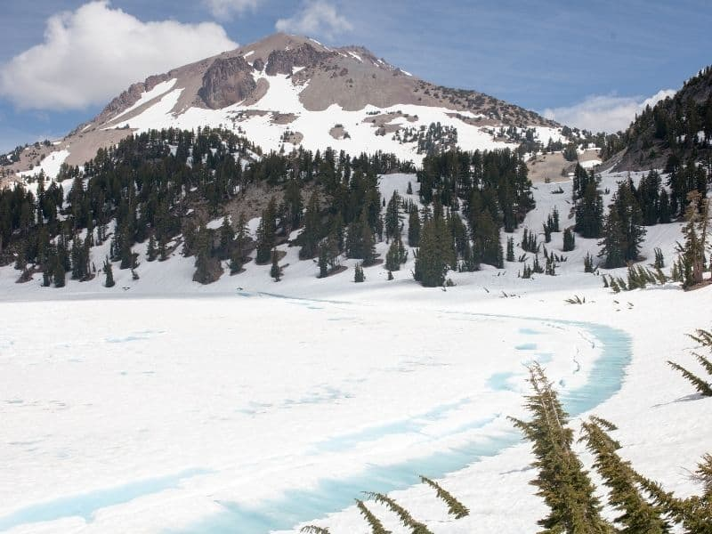 frozen lake at manzanita lake with a view of a snow covered mt lassen in the distance on a sunny day in winter