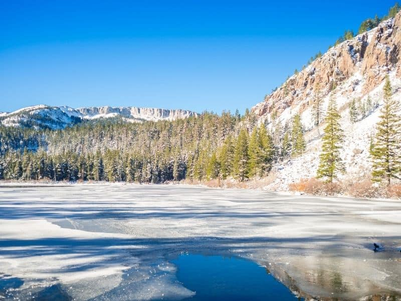 view from one of the lakes of mammoth lakes in winter, partially frozen over with snow on the ground