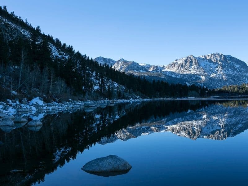 still unfrozen lake of june lake in winter, with snow on the rocks and on nearby mountains