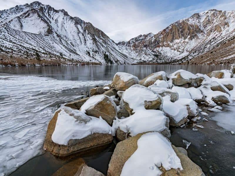 rocks covered in snow at the base of convict lake in the eastern sierras