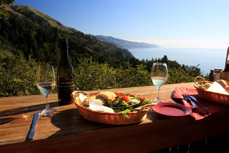 a salad and a bottle of wine with two glasses overlooking the pacific ocean at nepenthe