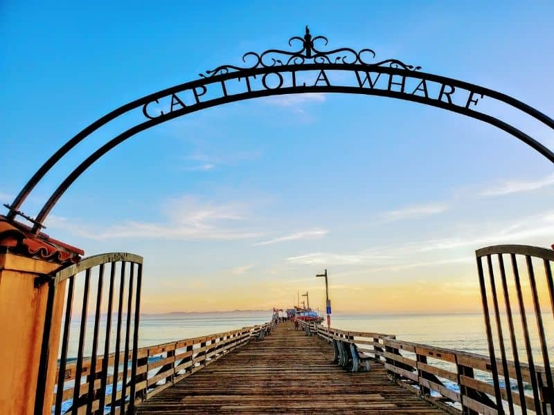arch sign saying capitola wharf leading out to a boardwalk over the water at sunset with a restaurant at the end