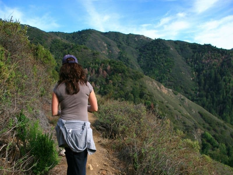 Hiker wearing a short sleeve shirt with a hoodie around her waist, showing how to wear layers in Big Sur