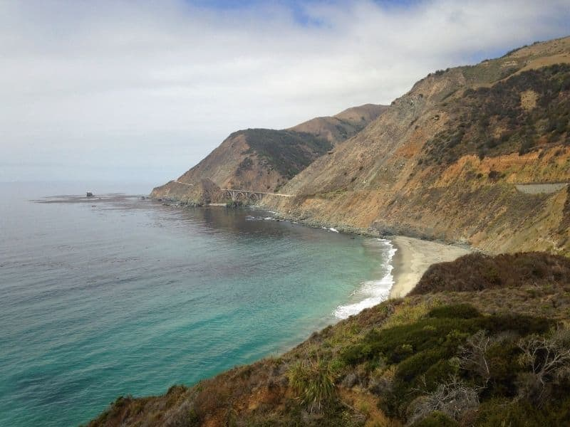 Big Sur on a partially cloudy day with brilliant turquoise water and the bridge visible in the far distance