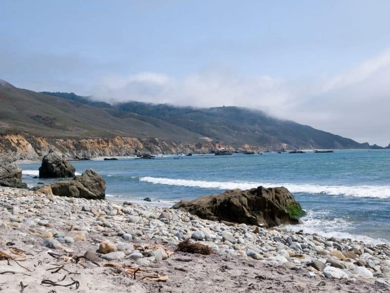 the shoreline at andrew molera beach with rocks at low tide so you can hike it