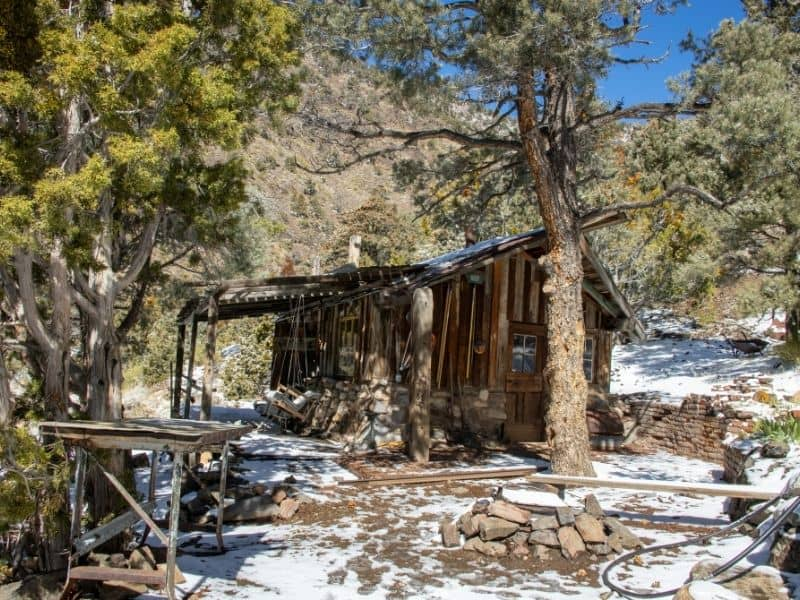 A wooden shack in Panamint City with some snow on the ground in winter