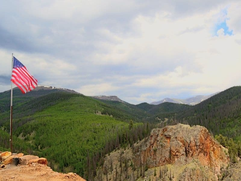 forested area around an old mine in northern california and an american flag