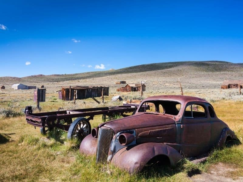 A rusted car, an old wagon, and old buildings abandoned to time in Bodie Ghost Town in California
