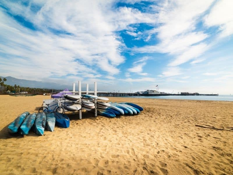 a stack of kayaks piled up for rent on the sandy beach near santa barbara, a beautiful kayaking spot in southern california