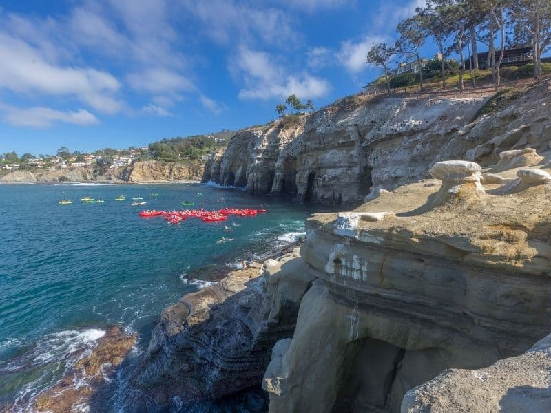 the area of la jolla sea caves with some groups of kayakers out and enjoying their day on the water