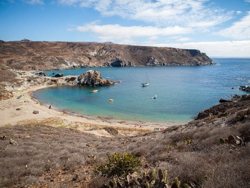 a peaceful bay with a half-moon beach in catalina island, with three small boats and a kayak out in the water
