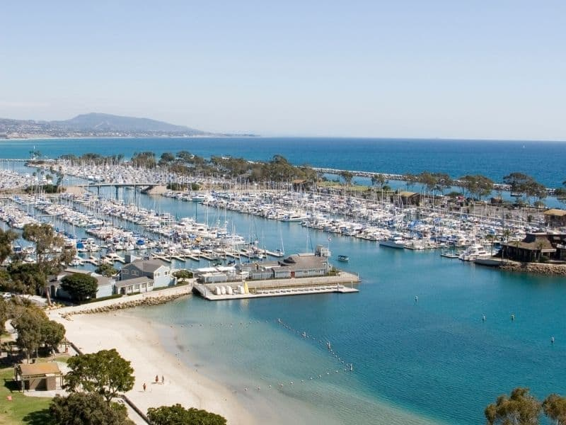 the soft white sand and blue waters of dana point california with harbor and boats nearby it -- a great launch for kayaking in southern california