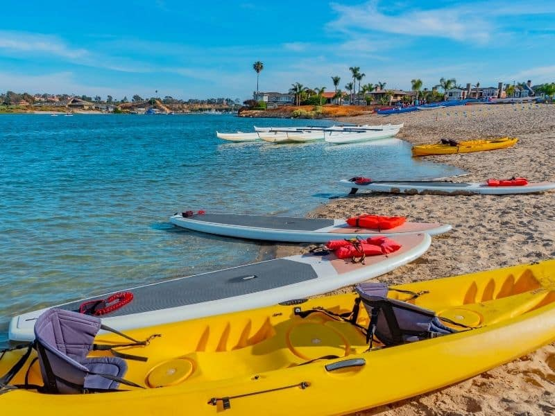 kayaks and paddleboards in newport beach in a variety of colors