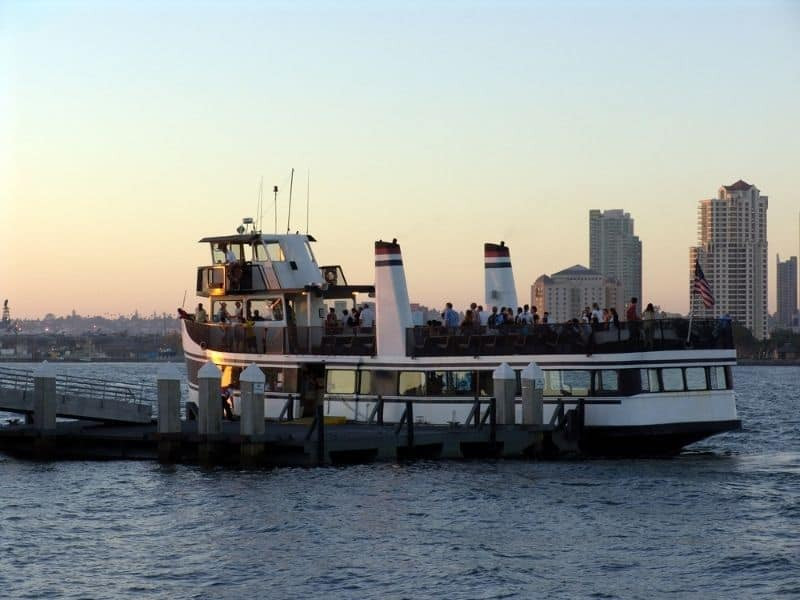 A boat of people boarding a harbor cruise boat in San Diego