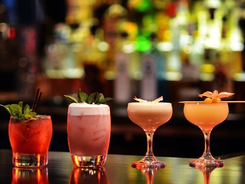 a selection of four pretty cocktails lined up in a row on the bar edge