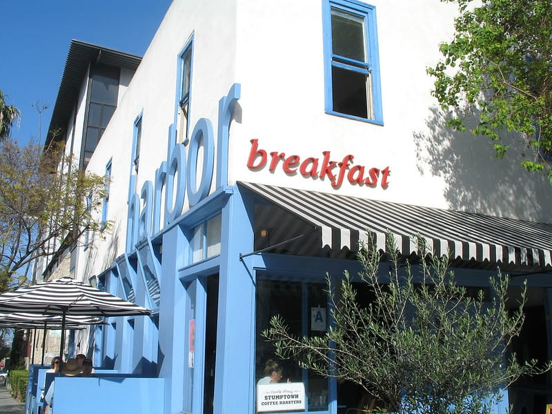 """White building with blue accent and shutters that says """"harbor breakfast"""" in LIttle Italy San Diego with shrubs and plants in front and black and white striped umbrellas"""