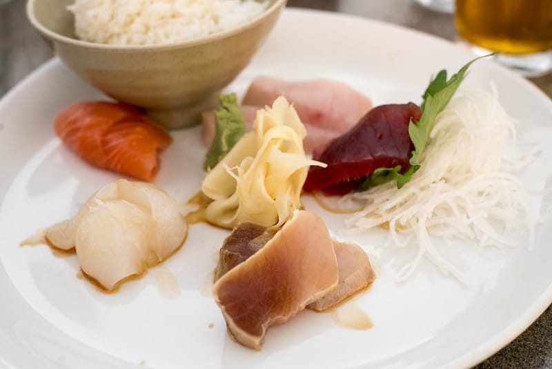 slices of fish with soy sauce and rice at a harborside restaurant on a weekend in long beach